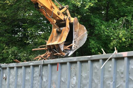 yellow excavator bucket dumping demolition waste into a truck Stock Photo - 7113370