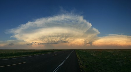 storm cell anvil head clouds above the great plains horizon just before sunset