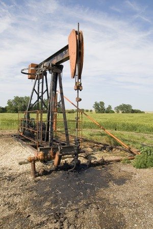 orange and black rusty oil well pump in a field