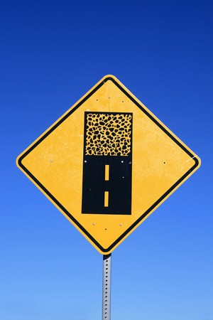 gravel road sign warning of a change from paved to unpaved road surface with blue sky background Stock Photo - 7392899