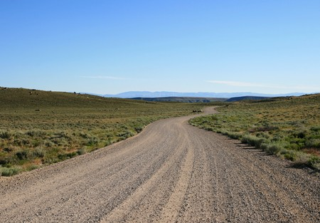 dirt road: a winding gravel road heads across the hills of Wyoming Stock Photo