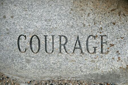 the word courage carved onto a granite cobble stone Stock Photo - 7565582