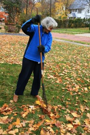 actieve senior vrouw harken bladeren op de voorkant gazon