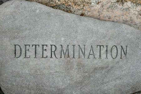 die Word-Bestimmung auf einem Granit Cobble Stein geschnitzt Lizenzfreie Bilder