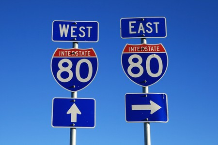 road signs for interstate 80 east and west with blue sky background Stock Photo