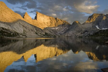 reflection of East Temple Peak and the Steeple in Deep Lake with evening alpenglow on the mountains, wind river range, wyoming Stock Photo - 7785211