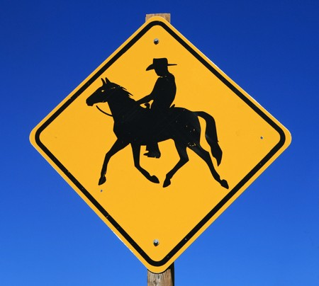 yellow and black horseback rider road sign with blue sky background Stock Photo - 7785217