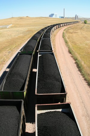 cars from a coal train lead off towards a distant power plant