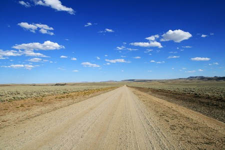 lonely dirt road runs across the Wyoming plains to a distant horizon with blue sky and clouds