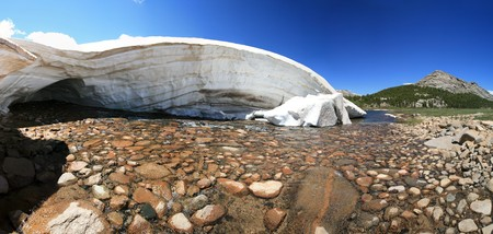 snowbank: stream emerging from under a melting snow bank in the Wind River Mountains, Wyoming Stock Photo