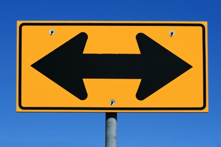 two sided black and yellow road sign designating two way traffic with a blue sky background Stock Photo