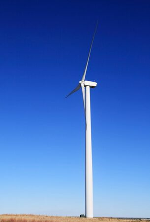 vertical image of tall white electric windmill or wind turbine on a flat prairie with blue sky background Banco de Imagens