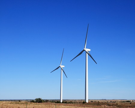 two white electric windmills or wind turbines on a flat prairie with blue sky background and copy space Stock Photo - 8161265