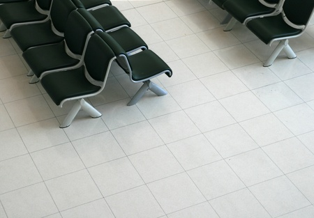 impersonal: waiting area with black padded seats and light tile floor from above