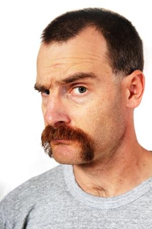 큰 콧수염이있는 사람이 보는 사람을보고 하나의 눈썹을 듭니다.