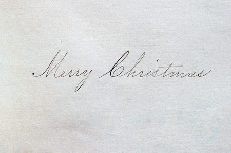 Merry Christmas written in cursive script on paper with an ink pen Stock Photo - 8334311