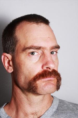 큰 콧수염과 회색 티셔츠를 입은 남자가 뷰어를 본다.