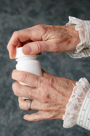 an old womans hands opening a white pill bottle photo