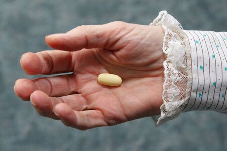 an old woman's hand holding a yellow pill in the palm Stock Photo - 8597840
