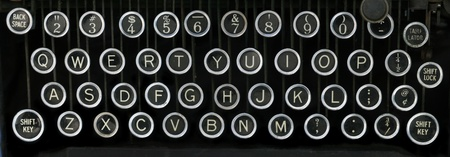 old typewriter keyboard with silver and black round keys with a black background