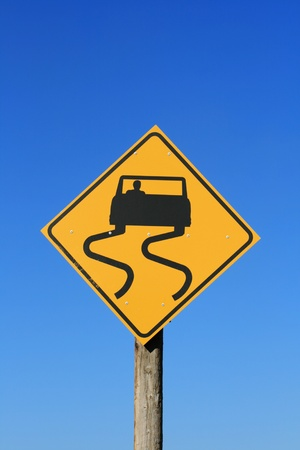 slippery road sign with car and skid marks in black on yellow with blue sky background