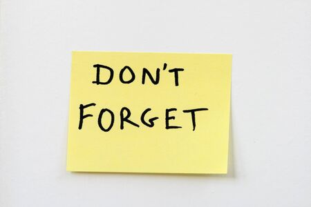 dont forget on a small yellow sticky note stuck on a white wall Stock Photo