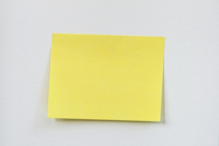 posted: closeup of a small blank yellow sticky note stuck on a white wall