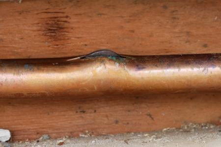 cobre: imagen de detalle de una tuber�a de agua cobre congelada y fisuras con hielo empujando fuera de la grieta Foto de archivo