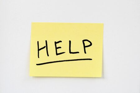 help written in black ink on a small yellow sticky note stuck on a white wall Stock Photo - 8721205