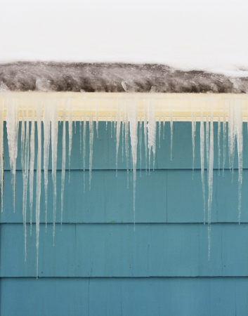 ice dam: icicles and ice dam on gutter damage a roof