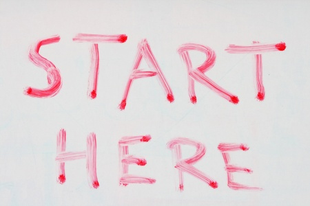 start here written in red dry erase marker on a used white board