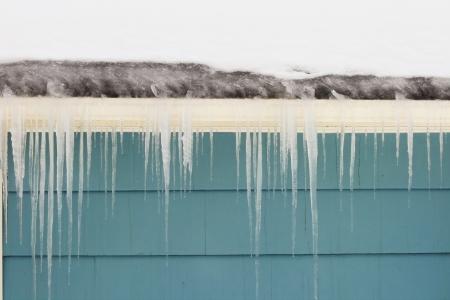 Ghiaccioli e diga di ghiaccio di grondaia danneggiano un tetto Archivio Fotografico - 8832094