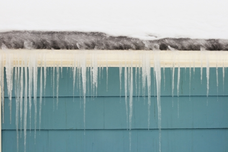 gutter ice dam and icicles damage a roof Stock Photo - 8832094