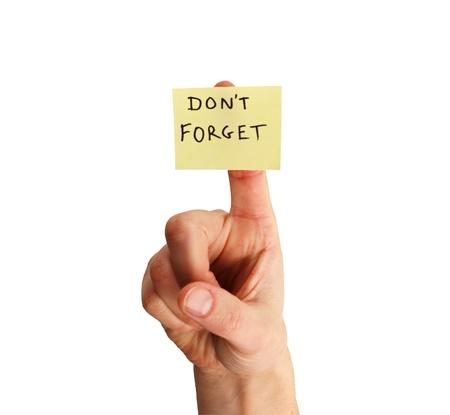 gele kleverige nota zeggen Vergeet niet op een vrouw vinger geïsoleerd op witte achtergrond Stockfoto