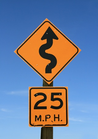 mph: old twisty road sign with 25 mph warning in yellow and black on blue sky background