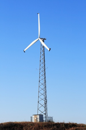 vertical image of tall electric windmill or wind turbine with blue sky background