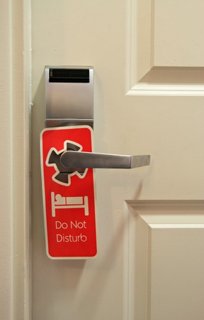 red do not disturb sign hanging on hotel door with digital key card lock photo