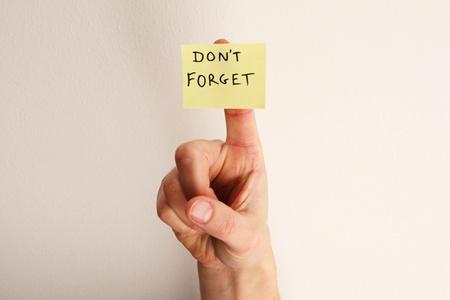 gele plaknotitie zeggen niet vergeten op de vinger van een vrouw met gebroken witte muur achtergrond Stockfoto