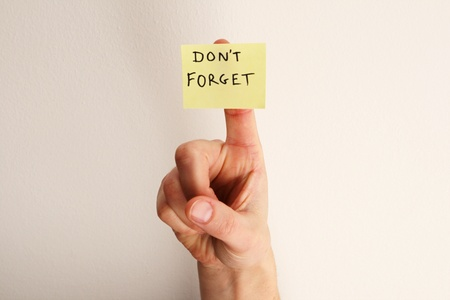 yellow sticky note saying dont forget on a womans finger with off-white wall background