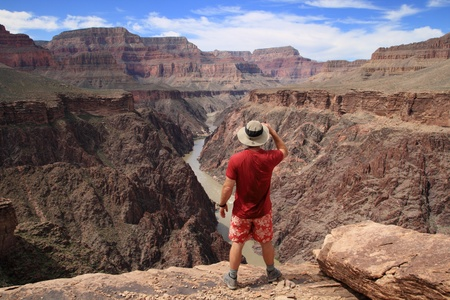 a hiker standing on an overlook in the Grand Canyon looking down into Granite Gorge from the Tonto Plateau Stock Photo - 9312113