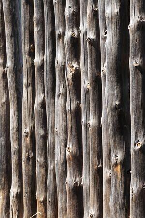 角度のついた: gray weathered vertical pine log fence angled image