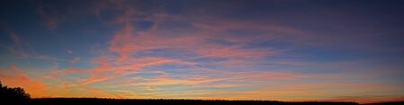 panorama of a sunset with blue sky and orange and yellow clouds Stock Photo - 9437049