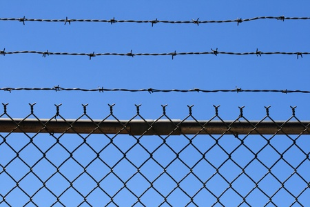 barbed wire and fence: chain link and barbed wire fence top with blue sky background