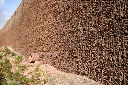 gabion: wire mesh and loose rock retaining wall with drain pipe perspective view
