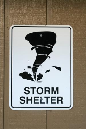 zwart en wit tornado storm schuilplaats teken op een bruine houten muur