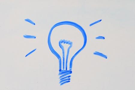 gloeilamp getekend in blauwe marker op een wit bord Stockfoto