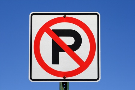 white red and black no parking sign with blue sky background