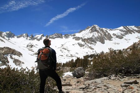 the back side of a male backpacker looking at snowy sierra mountains photo