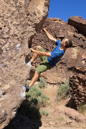 a man in a blue shirt bouldering on volcanic tuff rock