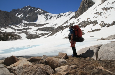 outdoorsman: backpacker by frozen Kearsarge Lake in the Sierra Nevada Mountains with University Peak in the background